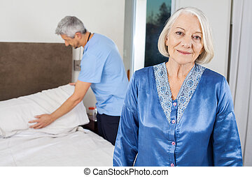 Senior Woman With Caretaker Making Bed At Nursing Home