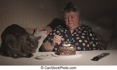 Elderly woman with her cat at the table eating together in front of TV at night