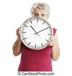 senior woman with clock - portrait of senior woman holding...