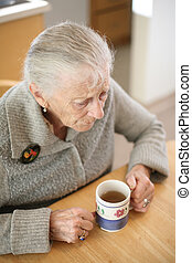 Senior woman with cup of tea at home. Shallow DOF.