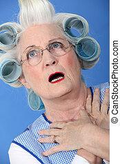 senior woman with curlers in her hair looking very surprised