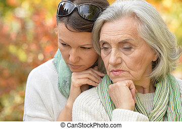 Senior woman with daughter in autumnal park