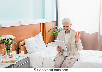 senior woman with digital tablet in hospital