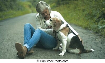 Senior woman with dog on a walk in green summer nature