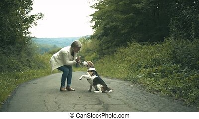 Senior woman with dog on a walk in green summer nature -...