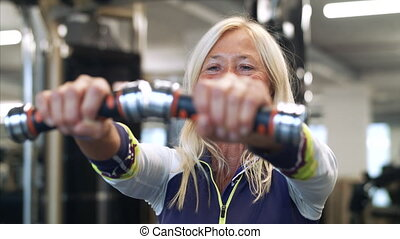 Senior woman with dumbbells in gym, doing exercise.