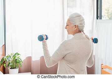 senior woman with dumbbells in hospital