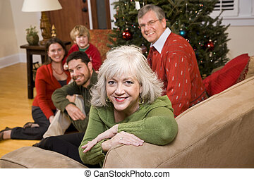 Senior woman with family by Christmas tree - three...