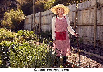 Senior woman with gardening tool in a vegetable garden