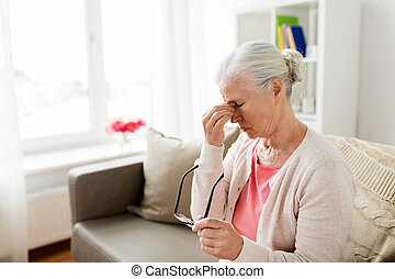 senior woman with glasses having headache at home