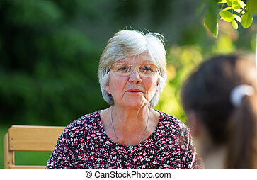 Grandmother talking to her granddaughter in park