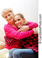 Senior woman with granddaughter or  daughter hugging on couch