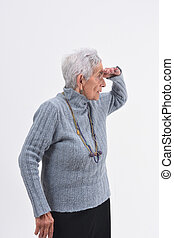 senior woman with hand in front looking away on white background