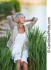 Senior Woman With Hands Behind Head Relaxing By Lakeside