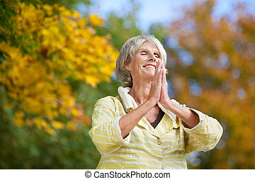 Senior Woman With Hands Clasped Meditating In Park - Low...
