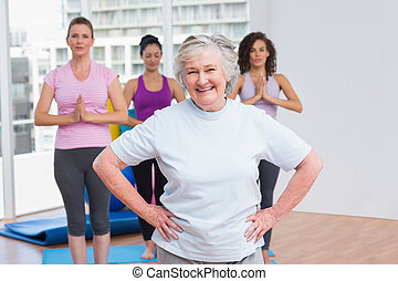 Senior woman with hands on hip standing in gym