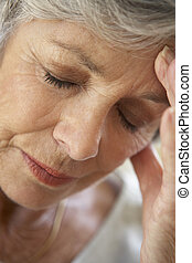Senior Woman With Head In Hands Looking Weary