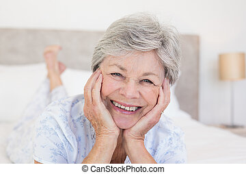 Senior woman with head in hands on