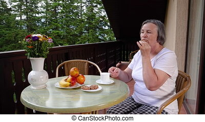 Senior woman with her coffee on terrace in summertime - Pan...
