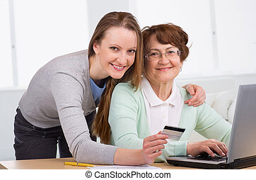 senior woman with her daughter online purchasing