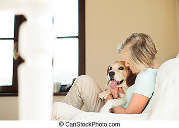 Senior woman with her dog at home relaxing