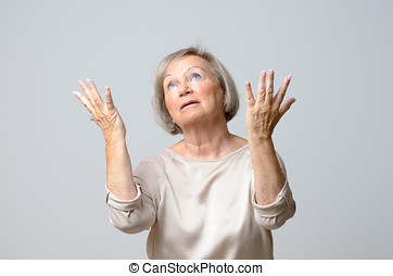 Senior woman with her hands up to the sky, standing with...
