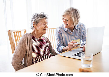 Senior woman with her mother with laptop at home.