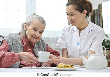 senior woman with home caregiver - Senior woman eats lunch...
