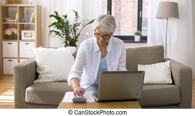 senior woman with laptop and calculator at home - business,...