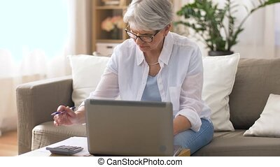 senior woman with laptop and calculator at home