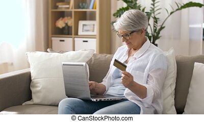 senior woman with laptop and credit card at home -...