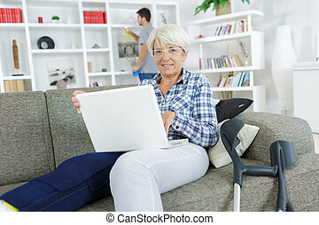 senior woman with laptop and injured leg at home