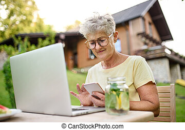 Senior woman with laptop and smartphone working outdoors in garden, home office concept.