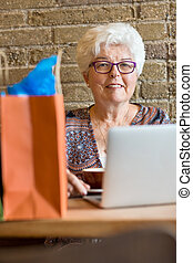 Senior Woman With Laptop In Coffeeshop