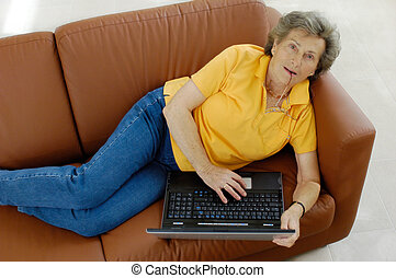 Senior woman with laptop on a couch