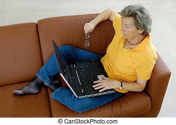 Senior woman with Laptop on Couch