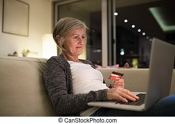 Senior woman with laptop sitting on the couch shopping online