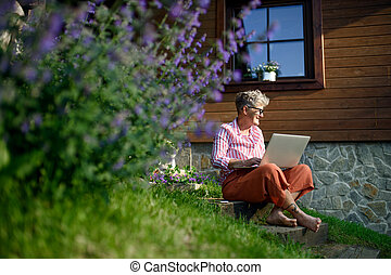 Senior woman with laptop working outdoors in garden, home office concept.