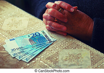 Senior woman with little euro money in front of her on table , toned image, colorized, selective focus, very shallow dof