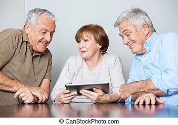 Senior Woman With Male Classmates Using Digital Tablet