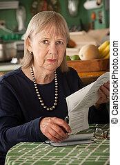 Senior woman with many bills