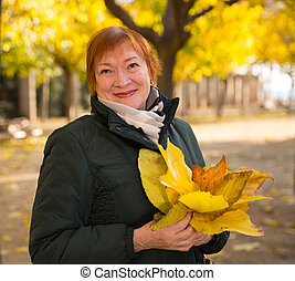 Senior woman with maple leaves walks in autumn park