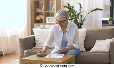senior woman with money and bills at home - finances,...