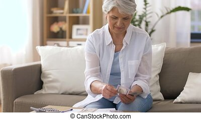 senior woman with money and bills at home