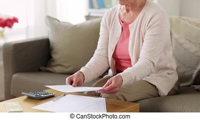 senior woman with money and papers at home - savings,...