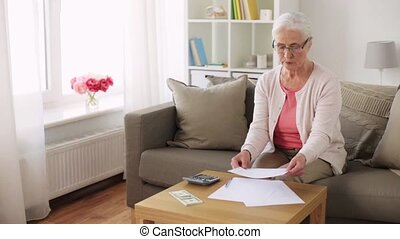senior woman with money and papers at home