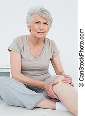 Senior woman with painful knee sitting on examination table...