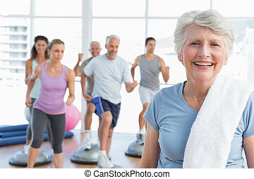 Portrait of a cheerful senior woman with people exercising in the background at fitness studio
