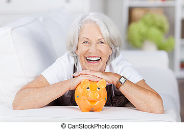 Senior Woman With Piggybank Lying On Sofa