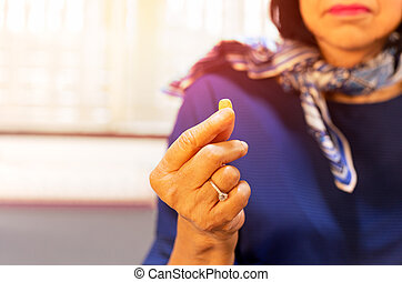 Senior woman with pill in her hand health care conceptual.